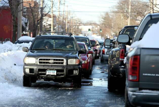 Gridlock traffic on East Main St. in Bridgeport, Conn. on Sunday Feb. 10, 2013.. Some major roads are plowed throughout city however not wide enough for two-way traffic. City officials still working around the clock to free residents from the effects of the weekend blizzard. Photo: Mike Ross / Connecticut Post freelance