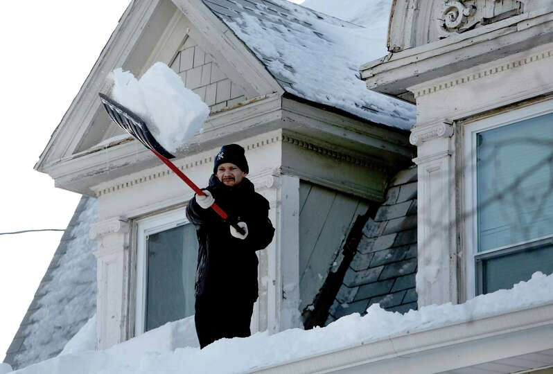 Noe Rodriguez works to remove snow of the roof of his home on the 1400 block of Noble Ave. in Bridge