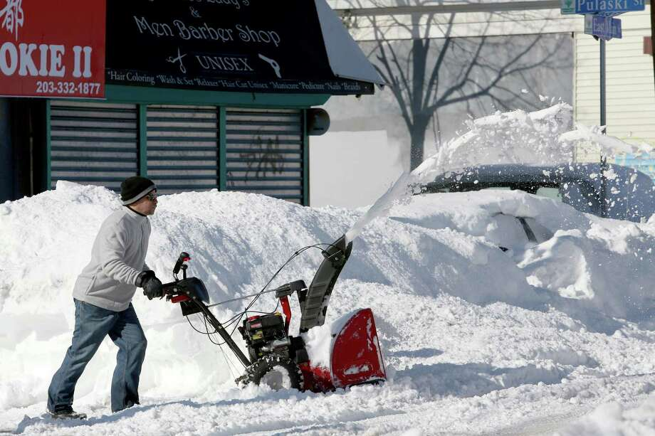 Rudy Taueras uses a snow blower to clear a path for customers at Torres VarietyY Grocery on East Main Street in Bridgeport, Conn. on Sunday Feb. 10, 2013. Photo: Mike Ross / Connecticut Post freelance