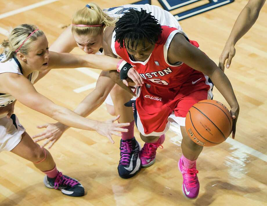 Houston guard Porsche Landry (5) controls a loose ball in a scramble against Rice guard Jessica Goswitz (5) and forward Megan Palmer (40) during the first half. Photo: Smiley N. Pool, Houston Chronicle / © 2013  Houston Chronicle
