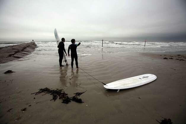 Surfers decide where they'll paddle into Gulf of Mexico to enjoy swells caused by the wind and current stormy weather on Sunday, Feb. 10, 2013, in Galveston. Photo: Mayra Beltran, Houston Chronicle / © 2013 Houston Chronicle