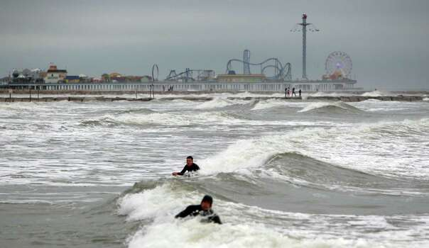 Surfers paddle back into Gulf of Mexico to enjoy the swells caused by the wind and current stormy weather on Sunday, Feb. 10, 2013, in Galveston. Photo: Mayra Beltran, Houston Chronicle / © 2013 Houston Chronicle