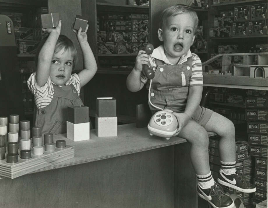 Even a freight train would have trouble smashing these durable toys. Julie Quayle, left, plays with stacking blocks, while brother William, 2, answers an Ambi phone, both from Splendid Childhood.Published March 24, 1984 Photo: E. Joseph Deering, Chronicle File