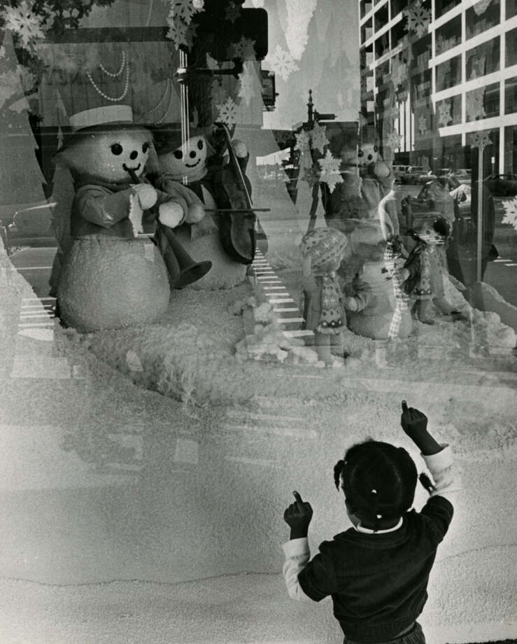 A youngster pauses to daydream of Santa Claus goodies at the Styrofoam winterland scene of downtown Foley s department store. Shop windows all over the city are springing forth with snowflakes and cardboard reindeer heralding the Christmas shopping season.Published Dec. 3, 1973 Photo: Orie Collins, Chronicle File