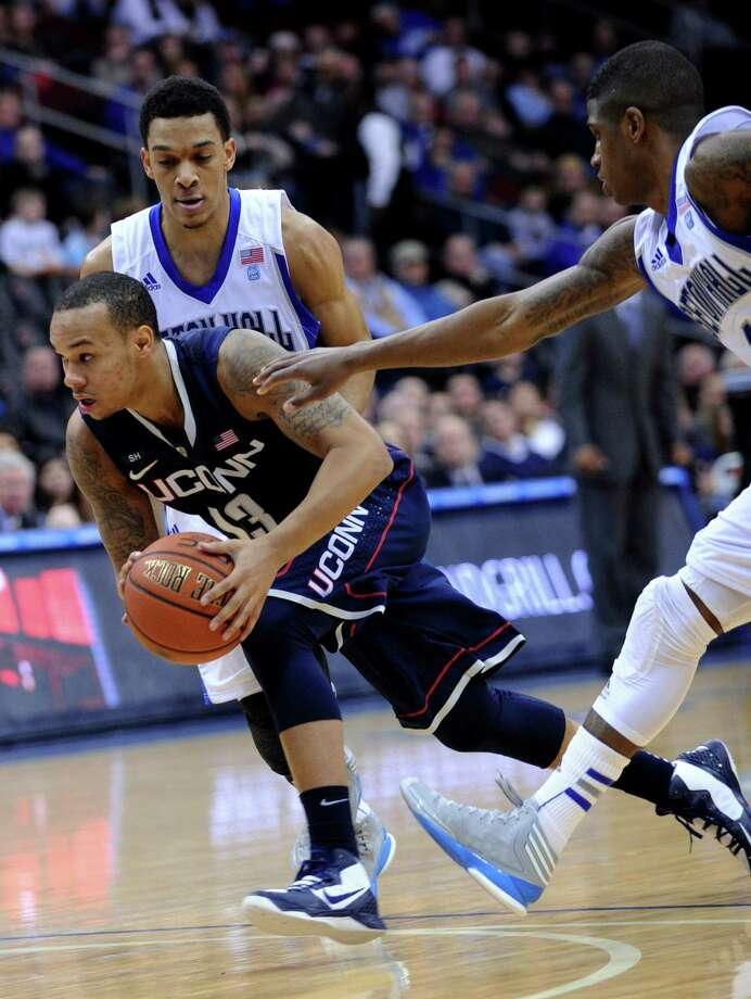 Connecticut's Shabazz Napier (13) drives to the basket between Seton Hall's Tom Maayan and Aaron Cosby, right, during the first half of an NCAA college basketball game Sunday, Feb. 10, 2013, in Newark, N.J. Connecticut won 78-67. (AP Photo/Bill Kostroun) Photo: Bill Kostroun, Associated Press / FR51951 AP