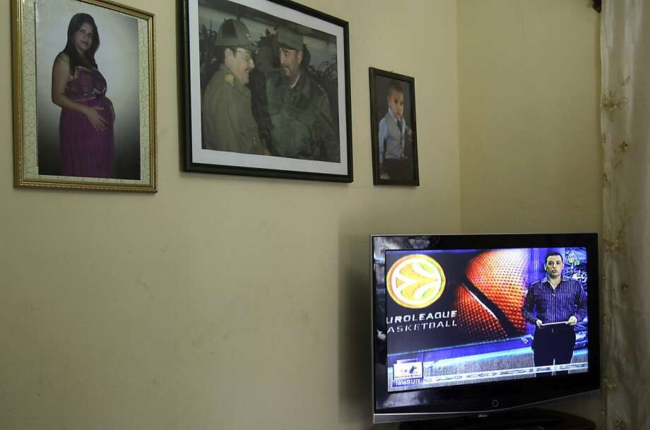 In this Feb. 1, 2013 photo, pictures of Cuban leader Fidel Castro and Cuba's President Raul Castro hang on the wall of a home as a television shows the Venezuelan channel Telesur in Havana, Cuba. Telesur, which is bankrolled primarily by Venezuela, has been broadcast live about 12 hours a day on the island's open airwaves since Jan. 20. Telesur's outlook may be sympathetic to Cuba's socialist model, but it's still a relatively unfiltered news source, and many say the decision to carry it here is as groundbreaking as other recent reforms, such as legalizing more private businesses or allowing greater travel freedom. Telesur was conceived as a force for regional integration and as a counterweight to Western channels such as CNN and the BBC. (AP Photo/Ismael Francisco, Cubadebate) Photo: Ismael Francisco, Associated Press
