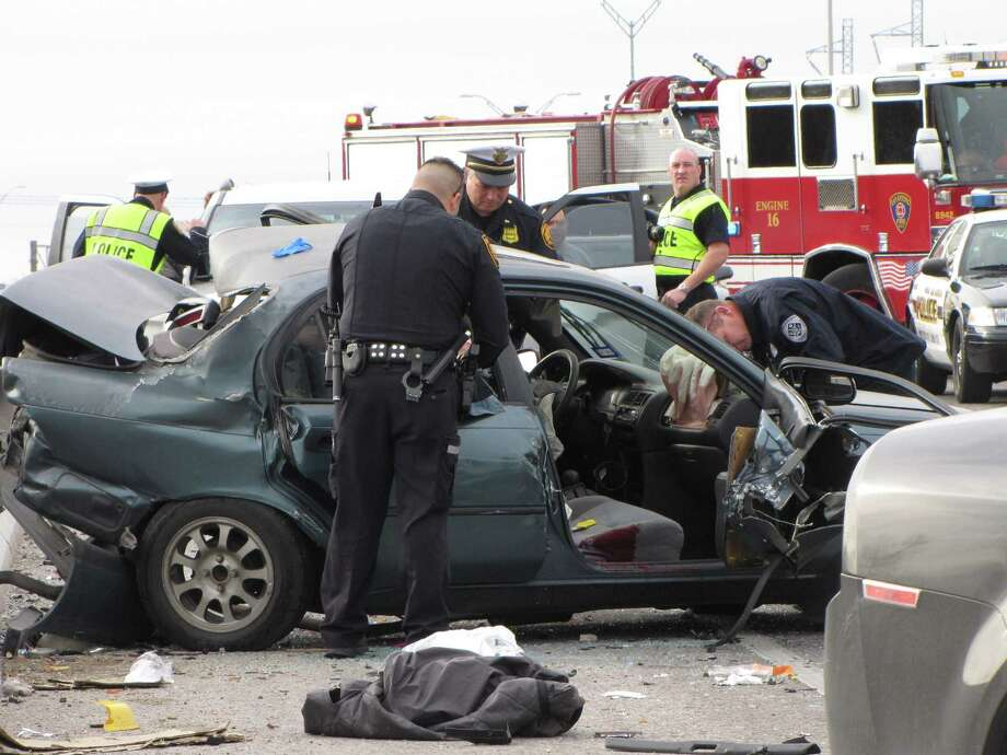 San Antonio police collect evidence from a car that was rear-ended by an off-duty deputy on the West Side Sunday afternoon, Feb. 10, 2013. The driver of the car, in his 40s or 50s, died at the scene of the crash. Photo: Eva Ruth Moravec, San Antonio Express-News