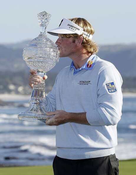 Brandt Snedeker poses for photographers and kisses his trophy on the 18th green of the Pebble Beach