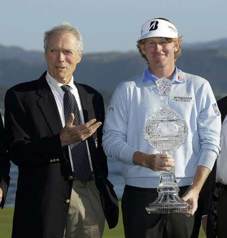 Film great Clint Eastwood, left, gestures toward Brandt Snedeker, right, after presenting him with his trophy on the 18th green of the Pebble Beach Golf Links following the AT&T Pebble Beach Pro-Am golf tournament, Sunday, Feb. 10, 2013, in Pebble Beach, Calif. Snedeker won the tournament after shooting a 7-under 65. Photo: Eric Risberg, Associated Press