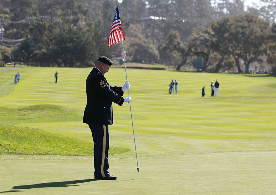 A serviceman tends the flagstick on the 16th green during the final round of the AT&T Pebble Beach National Pro-Am at Pebble Beach Golf Links on February 10, 2013 in Pebble Beach, California. Photo: Jed Jacobsohn, Getty Images
