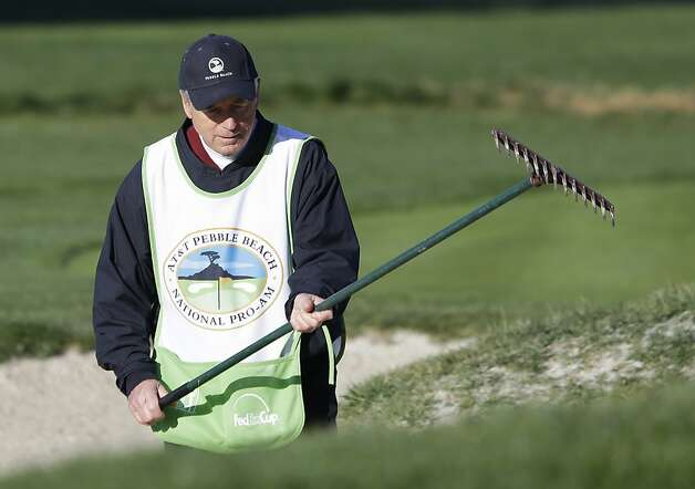 Former baseball commissioner and Olympic organizer Peter Ueberroth rakes a bunker on the second hole of the Pebble Beach Golf Links during the third round of the AT&T Pebble Beach Pro-Am golf tournament Saturday, Feb. 9, 2013, in Pebble Beach, Calif. Ueberroth was caddying for his daughter Heidi Ueberroth. Photo: Eric Risberg, Associated Press