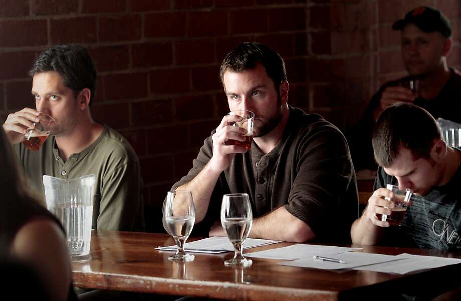 Nic Dominguez (left), Nick Jacoby and Matt Erdmann sample a German beer at the event. Photo: Brant Ward, The Chronicle