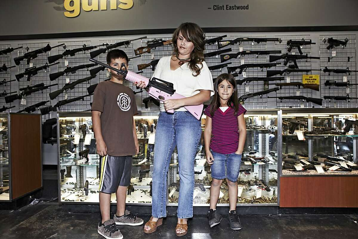 PHOENIX - MARCH 30: A mom holds a pink M-16 with her kids at the Gun Showroom in Phoenix on March 30, 2010 in Phoenix, Arizona. (Photo by Marc Lecureuil/Getty Images)