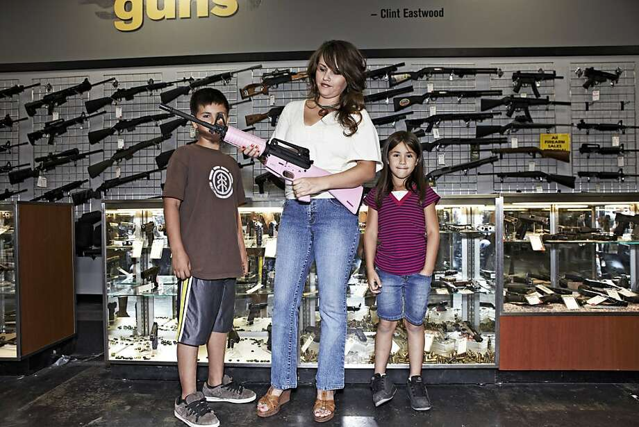 A mother holds a pink M16 rifle at a gun shop in Phoenix. Women are a major market for guns. Photo: Marc Lecureuil, Getty Images