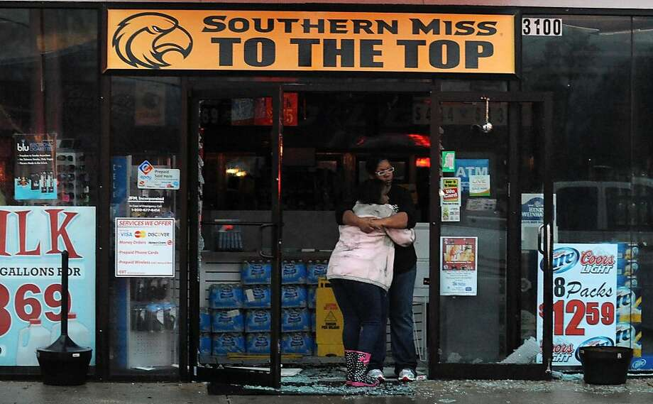 Two people console each other in the shattered doorway of a store in Hattiesburg, Miss., after the tornado passed through. The storm damaged several buildings on the University of Southern Mississippi campus, but no one was injured there. Photo: Ryan Moore, Associated Press