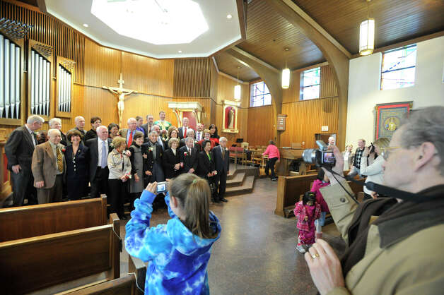 Parishoners photograph the 14 couples that were recognized at the Anniversary Mass at St. Leo Catholic Church in Stamford on Sunday, Feb. 10, 2013. Photo: Jason Rearick / The News-Times