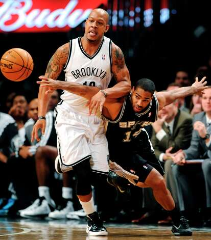 The Nets' Keith Bogans (10) and Spurs' Gary Neal (14) scramble for a loose ball in the first half Sunday, Feb. 10, 2013, at Barclays Center in New York. Photo: Kathy Kmonicek, Associated Press / FR170189 AP