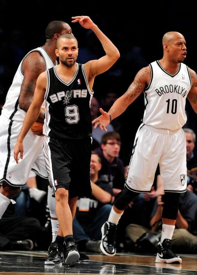 The Spurs' Tony Parker (9) and Nets' Keith Bogans (10) react after Parker scored in the first half  Sunday, Feb. 10, 2013, at Barclays Center in New York. Photo: Kathy Kmonicek, Associated Press / FR170189 AP