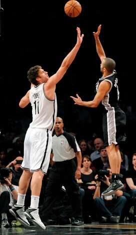 The Spurs' Tony Parker (9) shoots over the Nets' Brook Lopez (11) in the first half  Sunday, Feb. 10, 2013, at Barclays Center in New York. Photo: Kathy Kmonicek, Associated Press / FR170189 AP