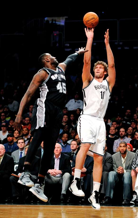 The Nets' Brook Lopez (11) shoots over the Spurs' DeJuan Blair (45) in the first half  Sunday, Feb. 10, 2013, at Barclays Center in New York. Photo: Kathy Kmonicek, Associated Press / FR170189 AP