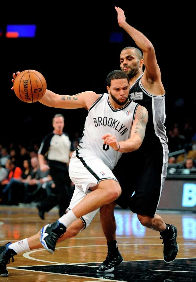 The Nets' Deron Williams (8) drives the ball around the Spurs' Tony Parker in the first half  Sunday, Feb. 10, 2013, at Barclays Center in New York. Photo: Kathy Kmonicek, Associated Press / FR170189 AP