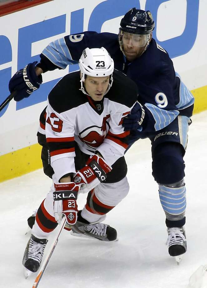 New Jersey's David Clarkson, who had two goals in the game, tries to evade Pittsburgh's Pascal Dupuis. Photo: Keith Srakocic, Associated Press