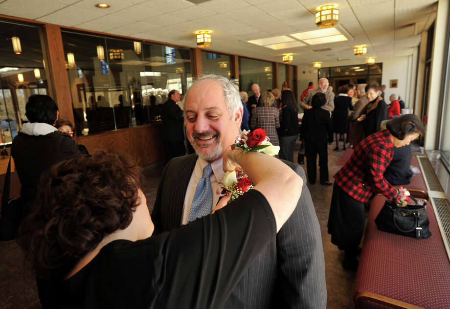 Gail Conti pins a corsage on her husband, Frank, before the Anniversary Mass at St. Leo Catholic Church in Stamford on Sunday, Feb. 10, 2013. The Contis will be celebrating their 25-year wedding anniversary this May. Photo: Jason Rearick / The News-Times