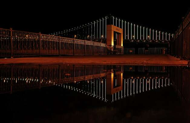 The Bay Bridge is reflected near Pier 14 as Leo Villareal's light show plays on Sunday, Feb.10. Villareal used 25,000 LED lights to illuminate the Bay Bridge for the Grand Lighting on March 5. Photo: James Tensuan, The Chronicle