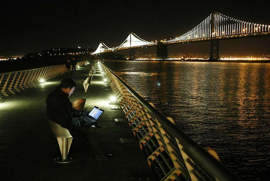 Leo Villareal works from his computer on Pier 14 to sequence lights on the Bay Bridge on Sunday. Photo: James Tensuan, The Chronicle
