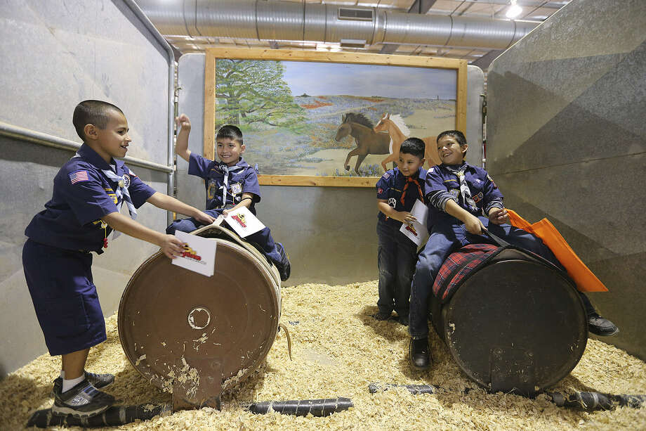 Daniel Cortez, 8 (from left), Jimmy Cuin III, 8, Julian Cuin, 6, and Nathan Rocha, 9, Cub Scouts from Windcrest Pack 157, enjoy Scout Day at the Rodeo on the fourth day of the San Antonio Stock Show & Rodeo. Photo: Photos By Jerry Lara / San Antonio Express-News