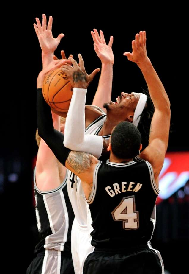The Nets' Gerald Wallace (45) is surrounded by the Spurs' Matt Bonner (15) and Danny Green (4) in the second half  Sunday, Feb. 10, 2013, at Barclays Center in New York. The Spurs won 111-86. Photo: Kathy Kmonicek, Associated Press / FR170189 AP