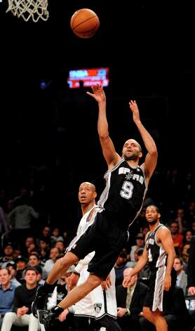 The Spurs' Tony Parker shoots in front of the Nets' Keith Bogans (10) in the second half  Sunday, Feb. 10, 2013, at Barclays Center in New York. The Spurs won 111-86. Photo: Kathy Kmonicek, Associated Press / FR170189 AP