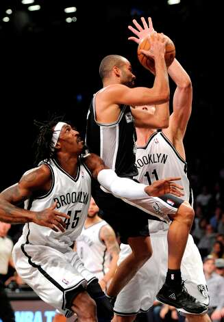 The Spurs' Tony Parker (9) drives the ball to the basket between the Nets' Gerald Wallace (45) and Brook Lopez (11) in the second half Sunday, Feb. 10, 2013, at Barclays Center in New York. The Spurs won 111-86. Photo: Kathy Kmonicek, Associated Press / FR170189 AP