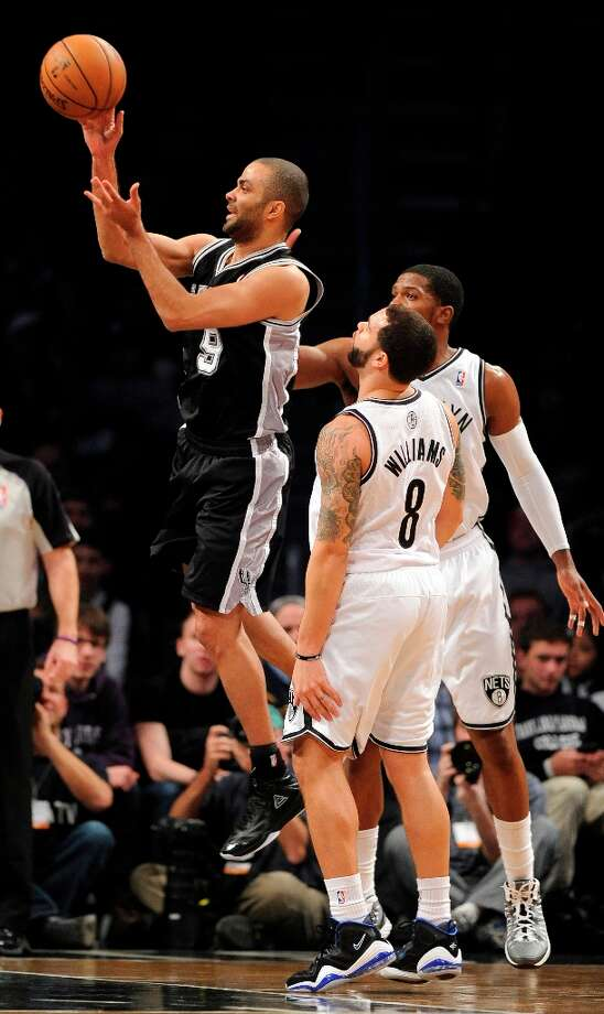 The Spurs' Tony Parker (9) shoots past the Nets' Deron Williams (8) and Joe Johnson in the first half Sunday, Feb. 10, 2013, at Barclays Center in New York. The Spurs won 111-86. Photo: Kathy Kmonicek, Associated Press / FR170189 AP