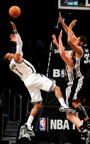 The Nets' C.J. Watson (1) leaps backward to shoot over the Spurs' Nando de Colo (25) and Boris Diaw (33) in the second half Sunday, Feb. 10, 2013, at Barclays Center in New York. The Spurs won 111-86. Photo: Kathy Kmonicek, Associated Press / FR170189 AP