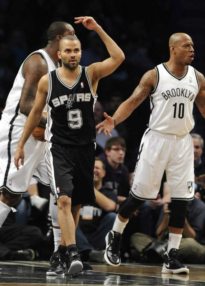 Spurs guard Tony Parker and Nets guard Keith Bogans show different reactions after Parker hit a first-half basket. Parker finished the game with 29 points, 11 assists and no turnovers. Photo: Kathy Kmonicek / Associated Press