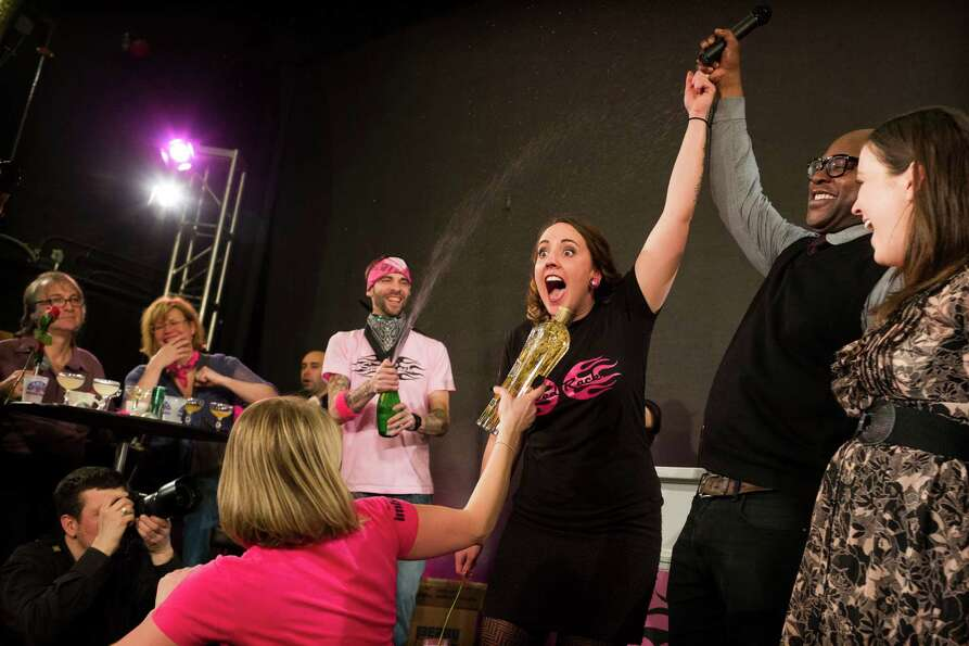 Portland resident and bartender Lacy Hawkins, center right, screams in surprise after winning the fi