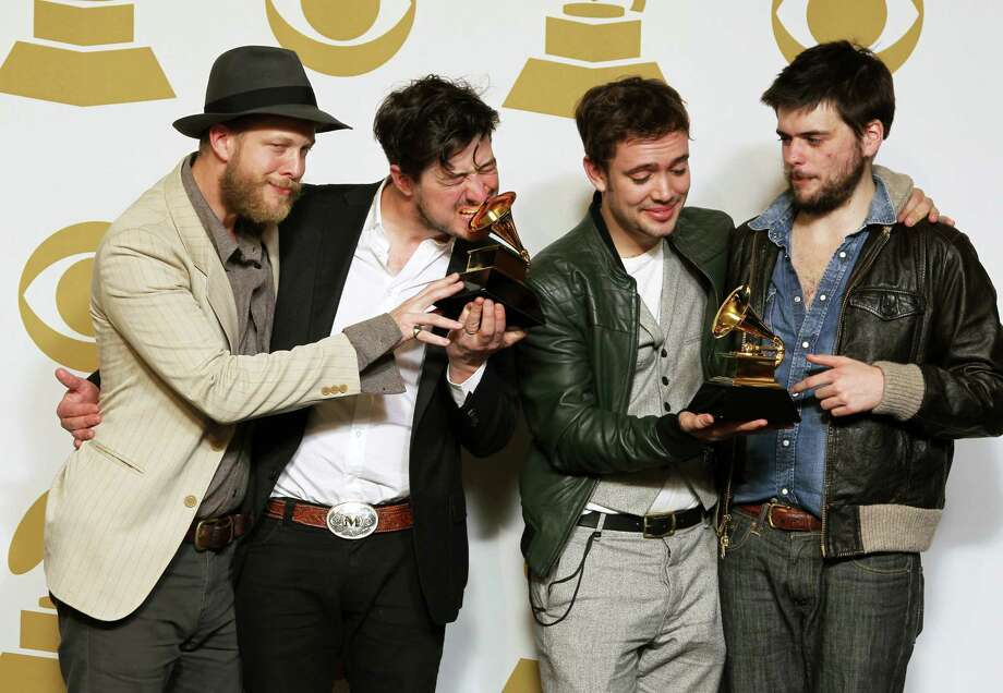 """Members of the musical group Mumford & Sons, from left, Ted Dwane, Marcus Mumford, Ben Lovett and Winston Marshall, pose backstage with the best long form music video award for """"Big Easy Express"""" and the album of the year award for """"Babel"""" at the 55th annual Grammy Awards on Sunday, Feb. 10, 2013, in Los Angeles. (Photo by Matt Sayles/Invision/AP) Photo: Matt Sayles"""