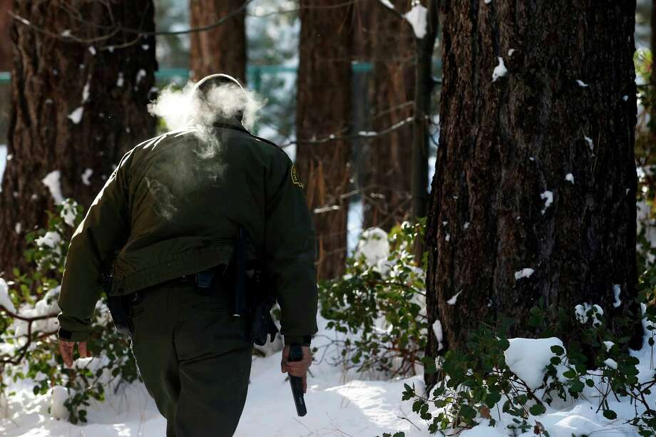 San Bernardino County Sheriff's officer Bernabe Ortiz holds a pistol as he searches a home for former Los Angeles police officer Christopher Dorner in Big Bear Lake, Calif, Sunday, Feb. 10, 2013. The hunt for the former Los Angeles police officer suspected in three killings entered a fourth day in snow-covered mountains Sunday, a day after the police chief ordered a review of the disciplinary case that led to the fugitive's firing and new details emerged of the evidence he left behind. (AP Photo/Jae C. Hong) Photo: Jae C. Hong