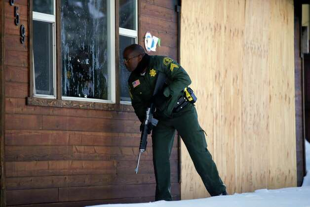 San Bernardino County Sheriff's officer Ken Owens searches a home for the former Los Angeles police officer Christopher Dorner in Big Bear Lake, Calif, Sunday, Feb. 10, 2013. The hunt for the former Los Angeles police officer suspected in three killings entered its fourth day in the snow-covered mountains on Sunday, a day after the police chief ordered a review of the disciplinary case that led to the fugitive's firing and new details emerged of the evidence he left behind. (AP Photo/Jae C. Hong) Photo: Jae C. Hong