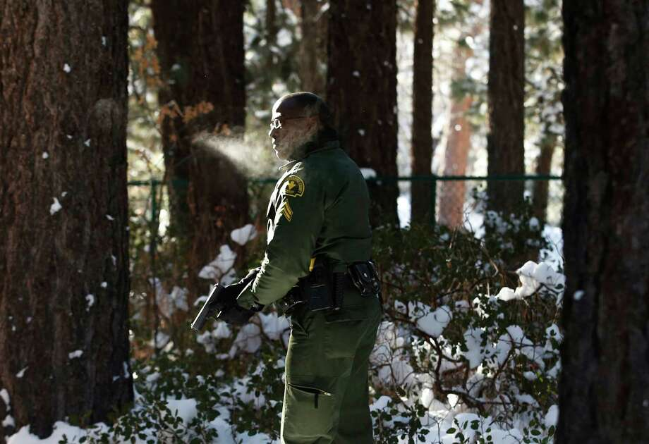 San Bernardino County Sheriff's officer Ken Owens searches a home for former Los Angeles police officer Christopher Dorner in Big Bear Lake, Calif, Sunday, Feb. 10, 2013. The hunt for the former Los Angeles police officer suspected in three killings entered a fourth day in snow-covered mountains Sunday, a day after the police chief ordered a review of the disciplinary case that led to the fugitive's firing and new details emerged of the evidence he left behind. (AP Photo/Jae C. Hong) Photo: Jae C. Hong