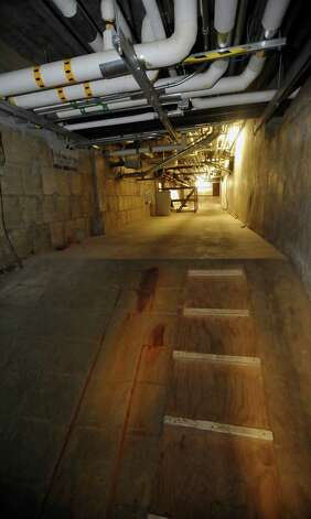 "I now am in the ""tunnels area"", also called the basement, that was used to circulate refrigerated air when the theatre was first built.   I have passed the junction that contained the air intake filters and have entered another area which runs below the lobby of the theatre. This area actually contains the tunnels that run under the seats in the theatre and blow air up through vents that can be found under the seats.  Every town has them, known as ""secret places,"" and they are usually off limits to the general public. You may have heard of them, wondered about them, but have never seen them, or you may not realize they exist at all.  One such place is the basement of the Jefferson Theater, where tunnel like walkways that were built originally as giant air ducts for the refrigerated air in one of the city's first buildings with central heat and air, still exist along with other small rooms. Dave Ryan/The Enterprise"