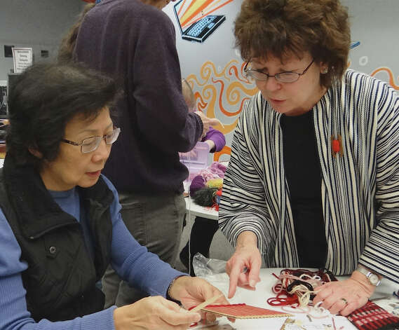 Handweavers Guild member Rebecca Arkenberg guides Fairfielder Lien Cao on the basics of handweaving Saturday at the Fairfield Woods Library.  FAIRFIELD CITIZEN, CT 2/2/13 Photo: Mike Lauterborn / Fairfield Citizen contributed