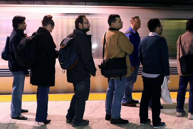 People wait for BART at the Embarcadero station on February 1st, 2013 in San Francisco, Calif. BART is planning on spending $650 million-plus to expand San Francisco's Embarcadero and Montgomery Street station platforms, knocking out the walls behind the trains and drilling new tunnels behind with access to the street. Embarcadero is very crowed during its peak time. Photo: Jessica Olthof, The Chronicle