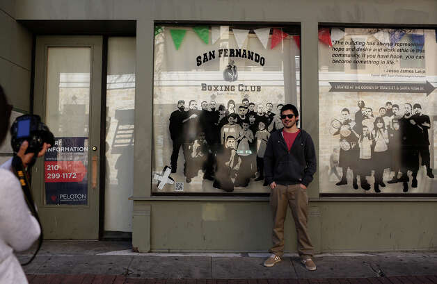 "Ignacio Palma, poses for Catalina Contesse, both of Chile, to take his picture in front of Rigoberto Luna's installation, ""Shadow Boxers,"" in the downtown storefront exhibition, part of the ""X Marks the Art"" program, in San Antonio on Friday, Feb. 8, 2013. Palma lives in a small town named San Fernando in Chile. Photo: Lisa Krantz, San Antonio Express-News / © 2012 San Antonio Express-News"