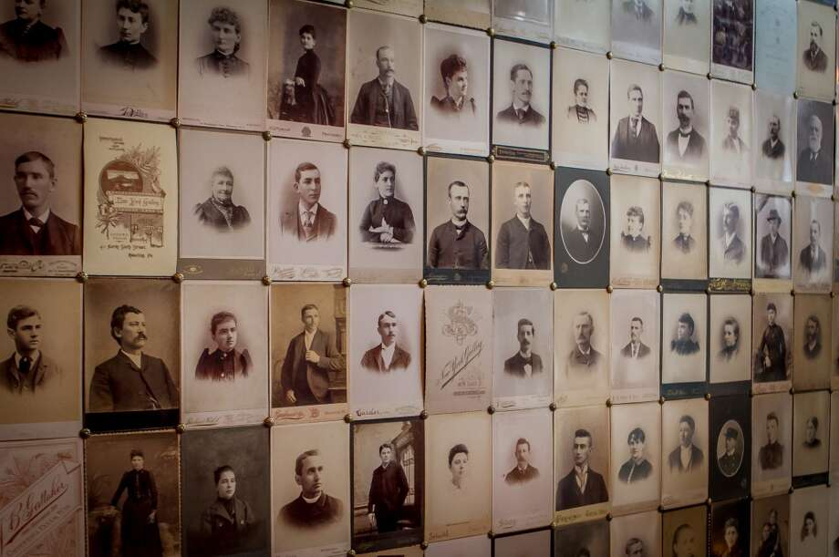 One wall is papered with daguerreotype portraits of men and women from the 1800s. The fixtures that hang from the ceiling have been converted from gaslights.