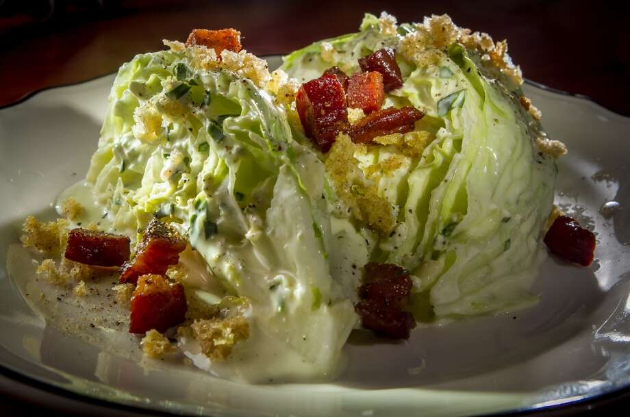 The wedge salad ($9) is two quarters of an iceberg head doused in Point Reyes blue cheese dressing with lardons and chives.