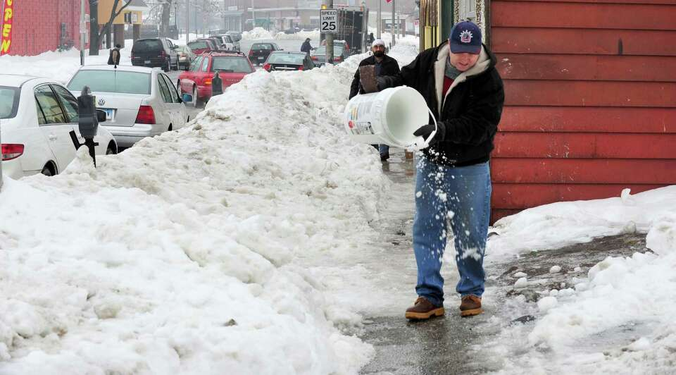 Sean Bishop spreads ice melt in front of Escape to the Arts on White Street in Danbury Monday, Feb.