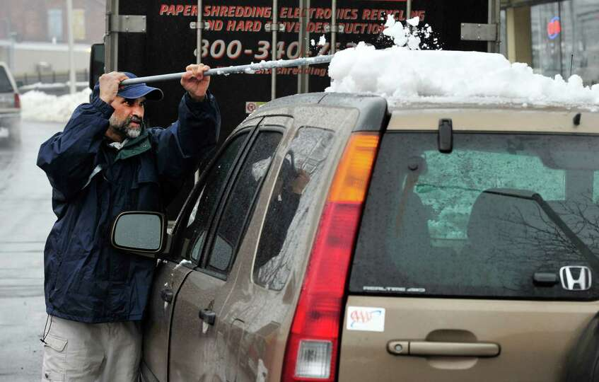 Milton De Almeida clears snow off his car parked on White Street in Danbury Monday, Feb. 11, 2012.