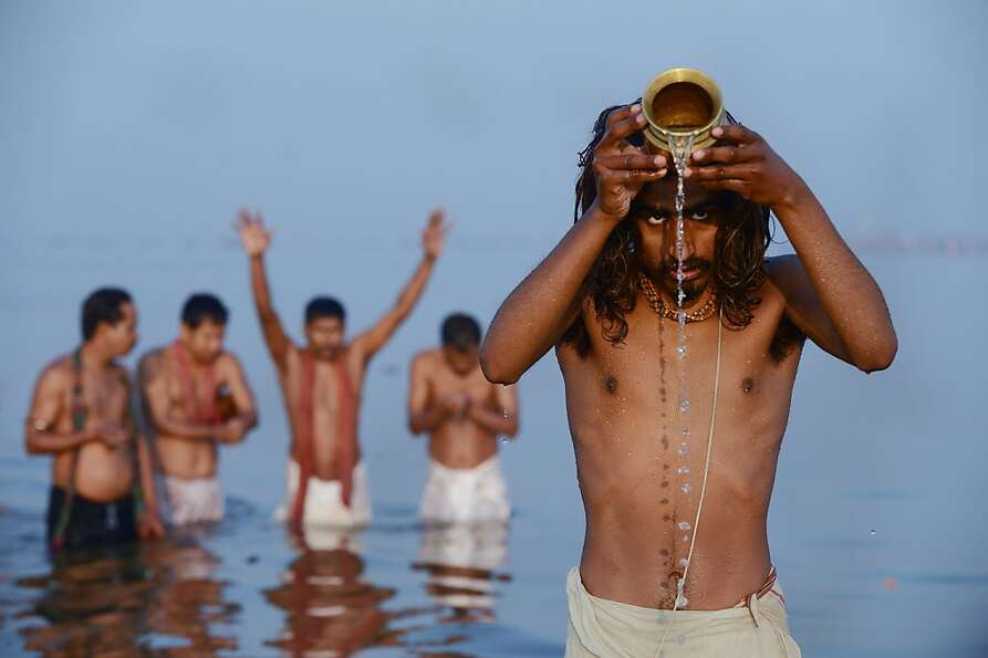 Hindu devotees pray as they bathe in the Sangam, the confluence of the Yamuna, Ganges and myt